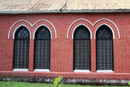 Window frame and red brick of exterior of main church at cathedral of the holy trinity, the church of the province of Myanmar.