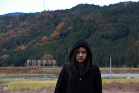 Asian woman in black clothing and hood standing outdoor with background mountain.