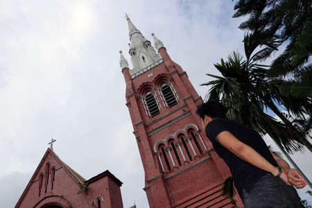 Behind of the man standing in front of the main building of church and church tower at cathedral of the holy trinity, the church of the province of Myanmar.
