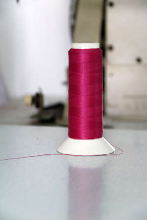 Dark pink thread in the thread roll put vertical on the sewing machine, through the use already from sewing garment and prepare to use again. It is a garment job for clothes and fashion. 版權商用圖片