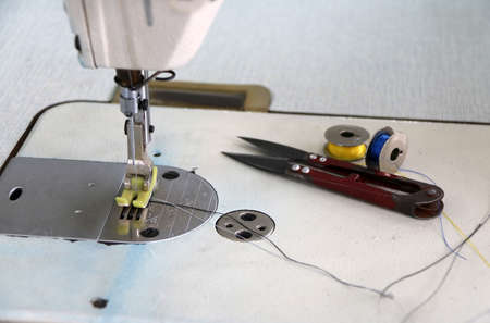 Sewing machine and sewing accessories, scissors Clippers with blue and yellow thread in the bobbins. it is a garment job for clothes and fashion.