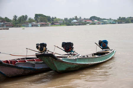 Three wooden boat machine landing on the water in the river. it is a small vessel propelled on water by an engine.