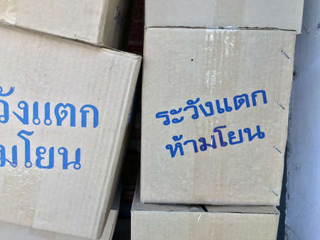 """Stack of paper box, grey color and blue color of text in Thai language """"Warning! Fragile, do not throw"""". pile up of gray box and metal Staples, wrapping with transparent tape. Stock Photo"""