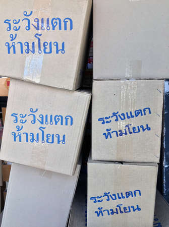 "Stack of paper box, grey color and blue color of text in Thai language ""Warning! Fragile, do not throw"". pile up of gray box and metal Staples, wrapping with transparent tape. Stock Photo"