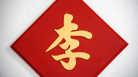 The surname sign on the white wall, The golden Chinese word handwriting style on the red wooden sign. (Chinese word : Lee, It is a surname)