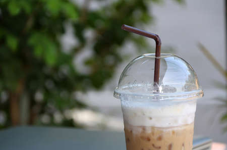 Close up ice coffee in the plastic cup with brown straw and out focus notebook, start work in a refresh morning. Stock Photo
