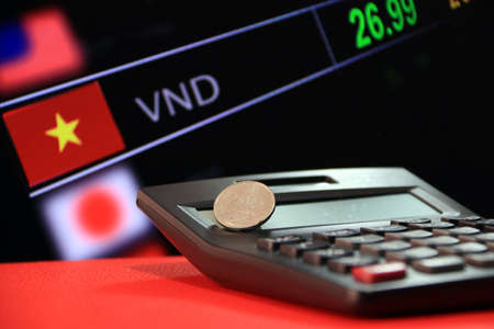 Two hundred Vietnam Dong coin on reverse (VND) on black calculator and red floor with digital board of currency exchange money background, the concept of finance.