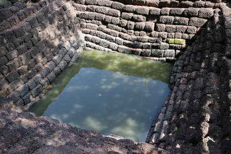 Square ancient pond, made from laterite stone in archaeological site of Srithep ancient town in Petchaboon, Thailand.