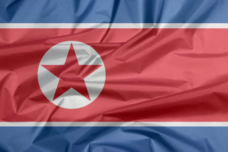 Fabric flag of North Korea. Crease of North Korean flag background, horizontal red white and blue, red star within a white circle. Foto de archivo