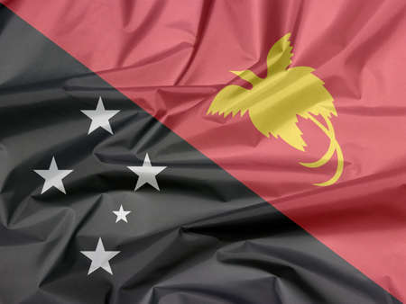 Fabric flag of Papua New Guinea. Crease of Papua New flag background, triangle is red with the soaring Raggiana Bird of Paradise and the lower triangle is black with the Southern Cross of white star. Foto de archivo