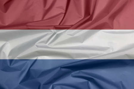Fabric flag of Netherlands. Crease of Holland flag background, red white and blue color.