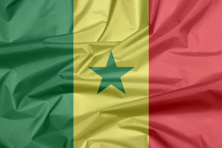 Fabric flag of Senegal. Crease of Senegalese flag background, green yellow and red; charged with a green five-pointed star at the centre.