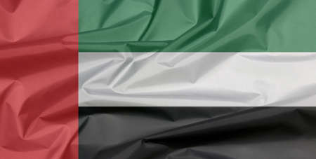 Fabric flag of United Arab Emirates. Crease of UAE flag background, green white and black with a vertical one fourth width red bar at the hoist. Stok Fotoğraf