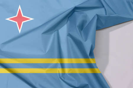 Aruba fabric flag crepe and crease with white space, a field of light blue and two narrow parallel horizontal yellow stripes in the bottom half and red star.