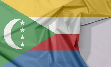 Comoros fabric flag crepe and crease with white space, yellow white red and blue with  green chevron, crescent and star. Stock fotó