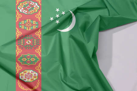 Turkmenistan fabric flag crepe and crease with white space, green field with red stripe containing five carpet guls stacked above two crossed olive branches; crescent and stars.