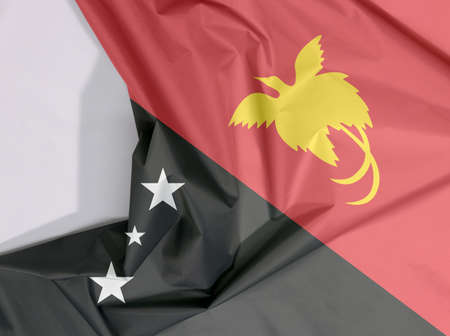 Papua New Guinea fabric flag crepe and crease with white space, triangle is red with the soaring Raggiana Bird of Paradise and the lower triangle is black with the Southern Cross of white star. Stock Photo