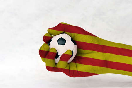 Mini ball of football in Catalunya flag painted hand on white background. Concept of sport or the game in handle or minor matter.