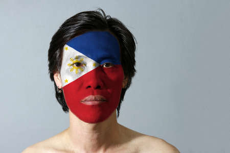 Portrait of a man with the flag of the Philippines painted on his face on black background. a horizontal blue and red; white equilateral triangle based at the hoist with star and sun.