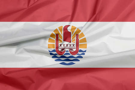 Fabric flag of French Polynesia. Crease of French Polynesia flag background. Two red horizontal and wide white; centered is a disk with Polynesian canoe rides on the wave.