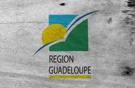 Flag of Guadeloupe Region on wooden plate background. Grunge Guadeloupe Region flag texture. sun and bird on a green and blue square with the subscript REGION GUADELOUPE underlined in yellow. Фото со стока