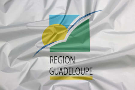 Fabric flag of Guadeloupe Region. Crease of Guadeloupe Region flag background. sun and bird on a green and blue square with the subscript REGION GUADELOUPE underlined in yellow. Фото со стока