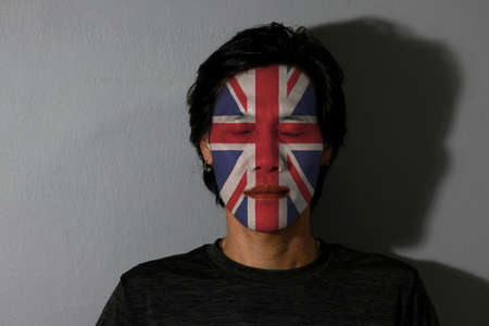 Portrait of a man with Union jack flag painted on his face and close eyes with black shadow on grey background. The concept of sport or nationalism. Standard-Bild