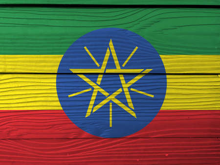 Flag of Ethiopia on wooden wall background. Grunge Ethiopian flag texture, tricolor of green yellow and red with the National Emblem.