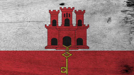 Flag of Gibraltar on wooden plate background. Grunge Gibraltar flag texture, White and red stripe with three towered and hangs a gold key. Standard-Bild
