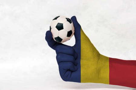 Mini ball of football in Romania flag painted hand, hold it with two finger on white background. Concept of sport or the game in handle or minor matter.