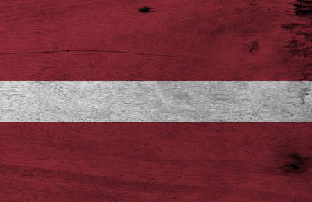 Flag of Latvia on wooden plate background. Grunge Latvian flag texture, a carmine field bisected by a narrow white stripe. Фото со стока