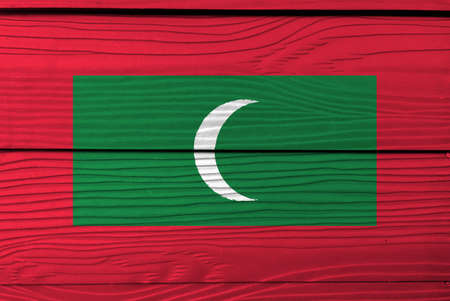 Flag of Maldives on wooden wall background. Grunge Maldives flag texture, green with red border and white crescent on center. Stok Fotoğraf