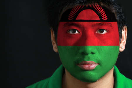 Portrait of a man with the flag of the Malawi painted on his face on black background, black red and green; charged with a red rising sun on black stripe.