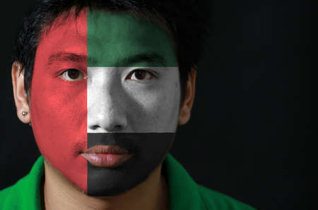 Portrait of a man with the flag of the United Arab Emirates painted on his face on black background, green white and black with a vertical one fourth width red. Stok Fotoğraf