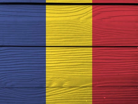 Flag of Romania on wooden wall background. Grunge Romanian flag texture, a vertical tricolor of blue yellow and red. Stock Photo