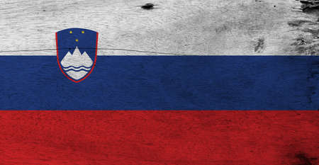 Flag of Slovenia on wooden plate background. Grunge Slovenian flag texture, White blue and red, charged with the Coat of arms at the hoist side. Stock fotó