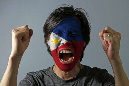 Cheerful portrait of a man with the flag of the Philippines painted on his face on grey background. The concept of sport or nationalism.
