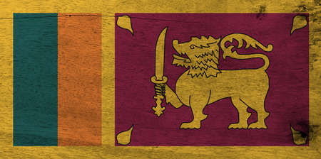 Flag of Sri Lanka on wooden plate background. Grunge Sri Lanka flag texture, four color of green orange yellow and dark red with golden lion.