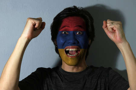 Cheerful portrait of a man with the flag of the Armenia painted on his face on grey background. The concept of sport or nationalism. horizontal tricolor of red, blue, and orange.