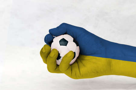 Mini ball of football in Ukraine flag painted hand on white background. Concept of sport or the game in handle or minor matter. horizontal bands of blue and yellow.