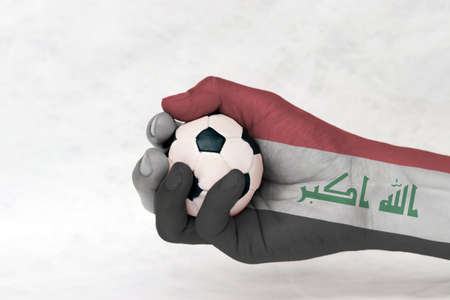 "Mini ball of football in Iraq flag painted hand on white background. Concept of sport or the game in handle or minor matter. red white and black with the ""God is greatest 免版税图像"