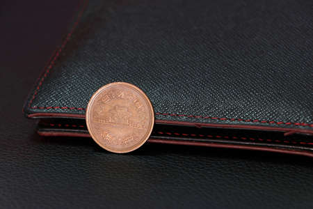 Japanese ten Yen coins on obverse (JPY) with black wallet on black floor, the concept of finance. 版權商用圖片