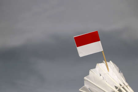 Mini Indonesia flag stick on the white shuttlecock on the grey background. Concept of badminton sport.