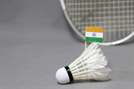 Mini India flag stick on the white shuttlecock on the grey background and out focus badminton racket. Concept of badminton sport.