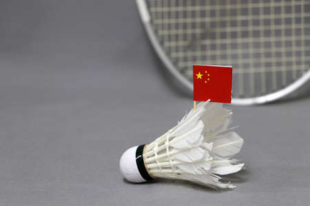 Mini China flag stick on the white shuttlecock on the grey background and out focus badminton racket. Concept of badminton sport. Stock Photo