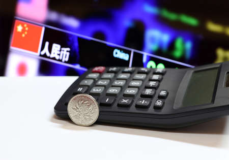 Chinese one Yuan coins on obverse (CNY) Chrysanthemum blossom, bank name ZHONGHUA RENMIN YINHANG on white floor and calculator with digital board of currency exchange money background.