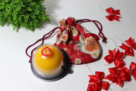Chinese language : bliss, stick on the orange cake on the red fabric bag and red ribbon and green leaf on white floor. Chinese New Year concept. 版權商用圖片