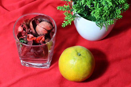 Orange and dried flower in the glass with green leaf on red floor. Chinese New Year concept. 免版税图像