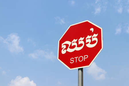 Traffic Signs, stop sign on blue sky background in Cambodian language and English.