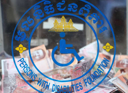 Logo of persons with disabilities foundation of Cambodia on the donation box and out focus Cambodian money.